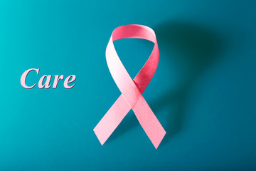 Pink breast cancer ribbon on blue background