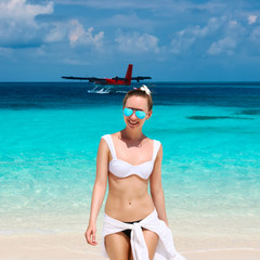 Woman at beach. Seaplane at background.