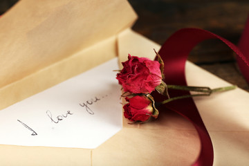 Envelope with love letter, vinous ribbon and dried rose