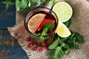 Pomegranate drink in glass with mint and slices of lime