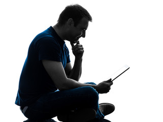 man sitting holding watching digital tablet  silhouette