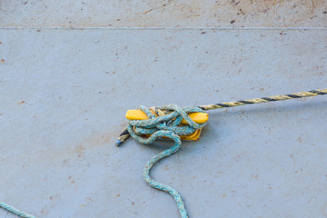 Old Blue Rope Tied to Yellow Cleat on Concrete Pier