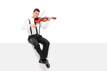 Male violinist playing seated on a blank panel