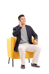 Man talking on a phone seated in a modern armchair