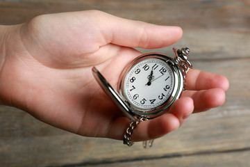 Silver pocket clock in hand on wooden background