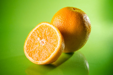 Orange, mandarin or tangerine fruit isolated on green background