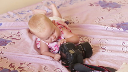 child in pink dress lay on the bed and play with black camera