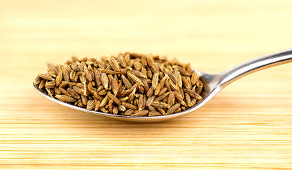 Spoonful of cumin seeds against wooden background