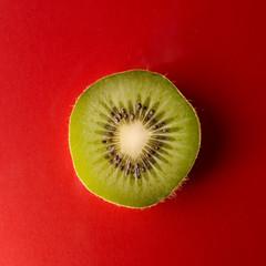 One slice of kiwi fruit isolated on red background