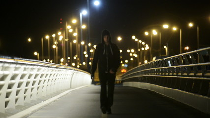 Man on bridge at night with lights