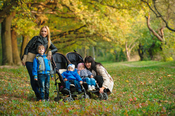 mothers with children twins on a walk in the autumn park