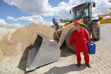 man in red uniform with petrol can,  bulldozer in background