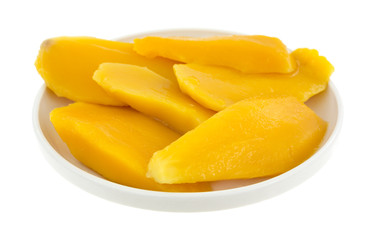 Mango slices in a small dish on a white background