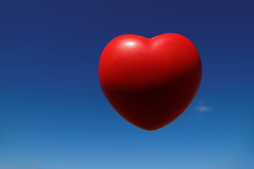 Red heart on a background of blue sky, deep blue
