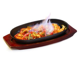Sizzling and burning fajitas on a frying pan