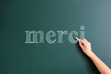 merci written on blackboard