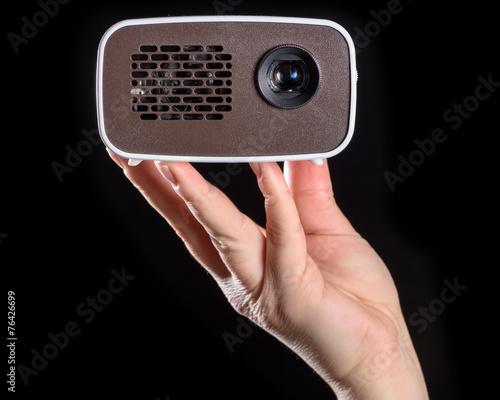 Mini Beamer in der Hand gehalten und freigestellt vor schwarzem - 76426699