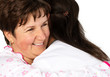 Senior woman and nurse hugging