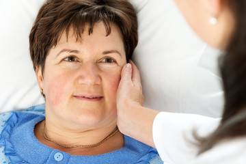 Smiling woman patient lying in bed
