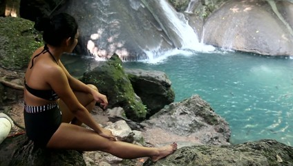 woman in retro swimsuit resting on the shore of the waterfall