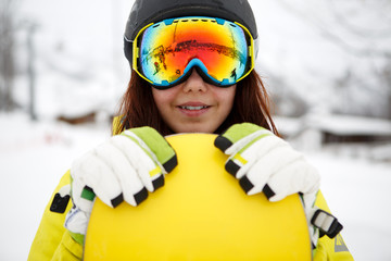 beautiful young woman posing outdoors with her snowboarding gear