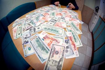 Urecognizable man counts money on kitchen table