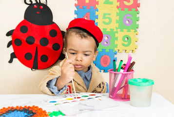 African American black boy drawing in preschool  in kindergarten