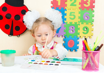 Cute child girl drawing at table in kindergarten