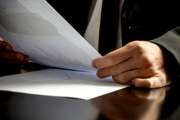 Close up of the hands of a business man analyzing business paper