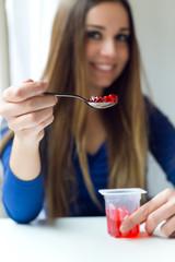 Young beautiful woman eating yogurt at home.