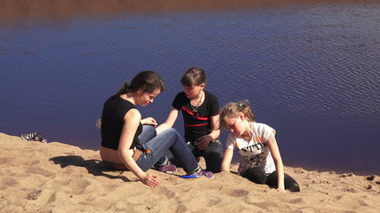 Mom and daughters on the sandy Bank of the river. 4K.