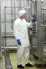 technician controlling industrial process in plant