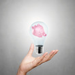 hand showing piggy bank with light bulb as concept