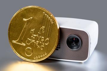 Mini Beamer mit goldener Euro-Münze zum Größenvergleich spieg
