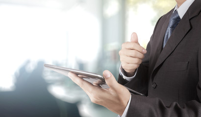 businessman hand using tablet computer and office background