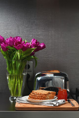 Toaster and bread with jam on the kitchen