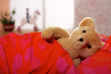 Teddy bear laying in bed