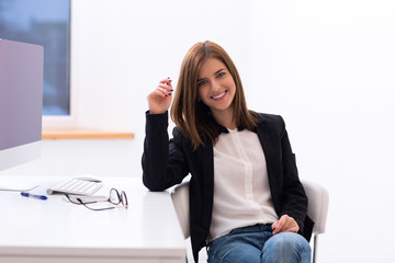 Happy businesswoman sitting in the office