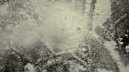 White flour pouring down black background