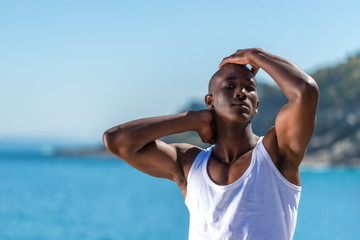 African black man wearing white vest and blue shorts