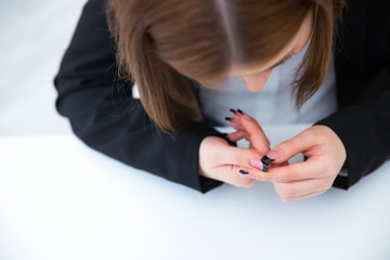 Busiensswoman caring for nails at her workplace