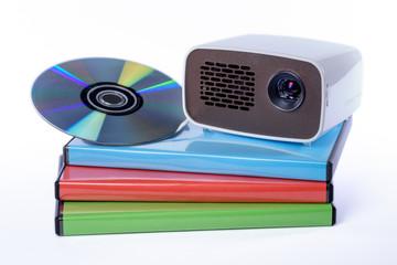 Mini Beamer mit DVD auf DVD-Hüllen freigestellt vor weißem Hin