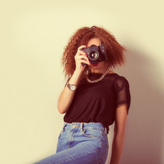 sexy woman with a camera in the hands of curly hair
