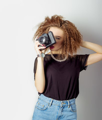 sexy woman in jeans with a camera in the hands of curly hair