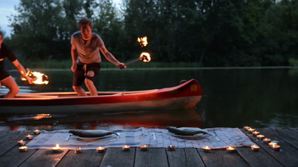 Two man with axe and torch moving on canoe