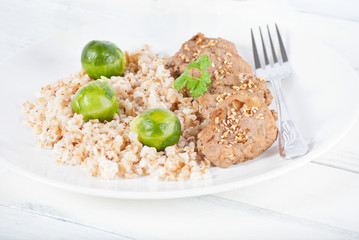 Medallions and brown rice with brussels sprouts on white wood