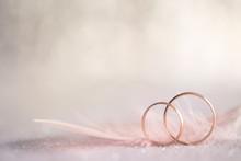 "Постер, картина, фотообои ""Two Golden Wedding Rings and Feather - gentle background"""