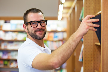 Man picking a book in a library