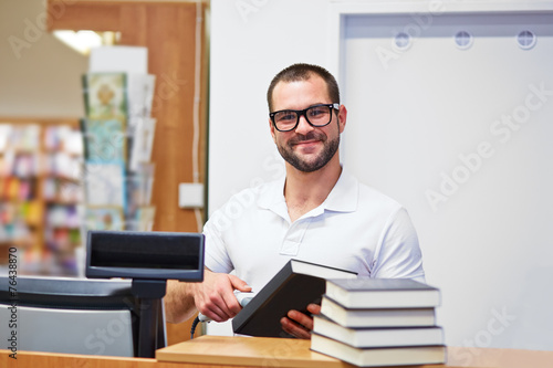Salesman at the checkout in a bookstore - 76438870