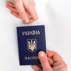 Ukrainian passport in hand on a white background